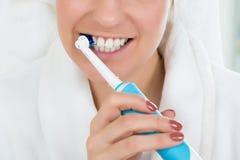Donna in denti di spazzolatura dell'accappatoio con lo spazzolino da denti elettrico fotografia stock libera da diritti