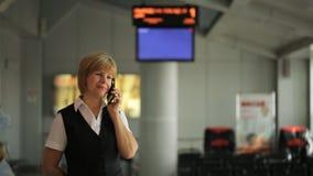 Donna dentro sala di attesa all'aeroporto che parla sul telefono stock footage