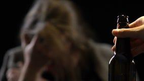 Donna depressa che grida esaminando bottiglia con la bevanda alcolica, abuso di sostanza archivi video