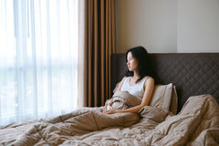 Donna depressa triste che pensa sul letto in camera da letto di lusso Immagini Stock