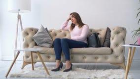 Donna depressa triste che si siede sul sofà in salone video d archivio
