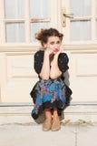 Donna deprimente e agitata che si accovaccia davanti alla casa Fotografia Stock Libera da Diritti