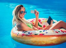Donna di abbronzatura di Njoying in bikini sul materasso gonfiabile nella piscina che usando compressa digitale e la carta di cre immagine stock