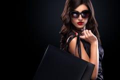 Donna di acquisto che giudica borsa grigia isolata su fondo scuro nella festa nera di venerdì Immagini Stock Libere da Diritti