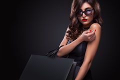Donna di acquisto che giudica borsa grigia isolata su fondo scuro nella festa nera di venerdì immagine stock