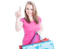 Donna di acquisto che sorride e che indica dito su a qualcosa Fotografie Stock