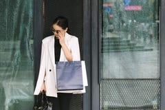Donna di acquisto in città, ritratto dei sacchetti della spesa alla moda della tenuta della giovane donna immagine stock libera da diritti
