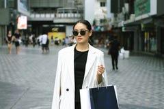 Donna di acquisto in città, ritratto dei sacchetti della spesa alla moda della tenuta della giovane donna immagini stock