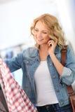 Donna di acquisto sul telefono Immagine Stock