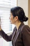 Donna di affari abbastanza asiatica che guarda attraverso i ciechi di finestra dell'ufficio Fotografia Stock Libera da Diritti