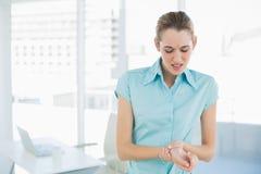 Donna di affari abbastanza giovane che afferra il suo polso danneggiato Immagine Stock