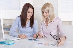 Donna di affari abbastanza giovane due che analizza il suo affare che guarda sa Immagine Stock