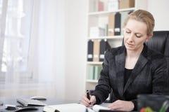 Donna di affari adulta alla sua scrittura dello scrittorio sulla carta Immagine Stock Libera da Diritti
