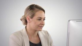 Donna di affari adulta che esamina computer in ufficio sul fondo di pendenza immagini stock