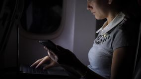 Donna di affari in aereo di linea che manda un sms in smartphone alla notte video d archivio