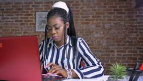 Donna di affari africana adulta sveglia che lavora al suo computer portatile mentre sedersi alla tavola ha messo a fuoco e si con stock footage