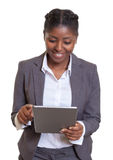 Donna di affari africana attraente che lavora con il computer della compressa Immagine Stock