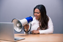 Donna di affari africana che grida in megafono sul computer portatile immagine stock libera da diritti