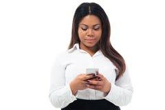 Donna di affari africana che per mezzo dello smartphone fotografie stock libere da diritti