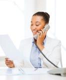 Donna di affari africana con il telefono in ufficio Fotografie Stock Libere da Diritti