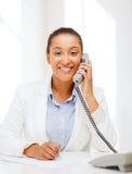 Donna di affari africana con il telefono in ufficio Fotografia Stock Libera da Diritti
