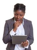 Donna di affari africana di pensiero con il computer moderno della compressa Fotografie Stock Libere da Diritti