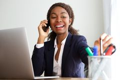 Donna di affari africana felice che parla sul telefono cellulare in ufficio fotografia stock