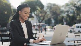 Donna di affari afroamericana sorridente che si siede in caffè sul terrazzo di estate, sul caffè bevente e lavorante al computer  archivi video