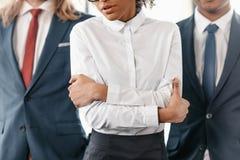 Donna di affari afroamericana turbata e due uomini d'affari che stanno nell'ufficio Immagine Stock