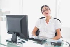 Donna di affari aggrottante le sopracciglia che si siede al suo scrittorio che esamina computer Fotografia Stock