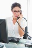 Donna di affari aggrottante le sopracciglia che si siede al suo scrittorio che parla sul telefono Fotografia Stock