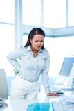 Donna di affari aggrottante le sopracciglia con la condizione di dolore posteriore Fotografia Stock Libera da Diritti