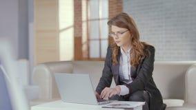 Donna di affari alla moda che lavora nell'ufficio di lusso, scrivente sul computer portatile stock footage