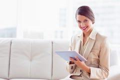 Donna di affari alla moda che si siede sul sofà facendo uso della compressa che sorride alla macchina fotografica Fotografia Stock
