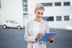 Donna di affari alla moda sorridente che per mezzo della compressa digitale fotografie stock