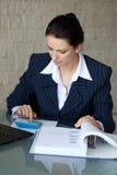 Donna di affari alla moda sorridente che si siede al suo scrittorio facendo uso di un calcul Fotografia Stock
