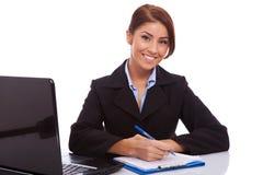 Donna di affari alla sua scrittura dello scrittorio Fotografia Stock