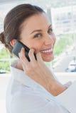 Donna di affari allegra che ha una conversazione telefonica Immagine Stock
