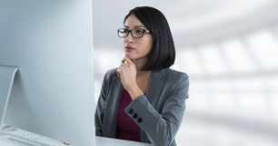 Donna di affari allo scrittorio con copmuter con fondo luminoso Fotografia Stock Libera da Diritti