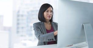 Donna di affari allo scrittorio con il computer con fondo luminoso Immagine Stock Libera da Diritti