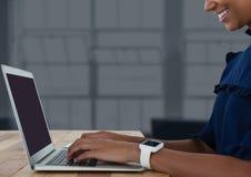 Donna di affari allo scrittorio con il computer portatile con fondo scuro Fotografia Stock Libera da Diritti