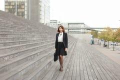 Donna di affari americana che sta sulle scale con la borsa e sulle alte costruzioni nel fondo Immagine Stock