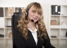 Donna di affari amichevole che indossa una cuffia avricolare fotografie stock libere da diritti