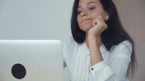 Donna di affari annoiata che lavora al computer portatile in ufficio video d archivio