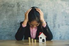 Donna di affari di ansia con la casa di modello e monete sullo scrittorio Immagini Stock Libere da Diritti
