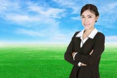 Donna di affari, armi attraversate, con il campo di erba verde e la s blu Fotografie Stock