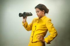 Donna di affari asiatica abbastanza giovane in vestito giallo tenendo il binocolo. Immagini Stock Libere da Diritti