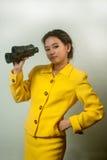 Donna di affari asiatica abbastanza giovane in vestito giallo tenendo il binocolo. Fotografia Stock