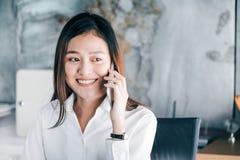 Donna di affari asiatica che parla sul telefono cellulare davanti al computer portatile c immagini stock libere da diritti