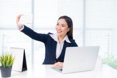 Donna di affari asiatica che prende un selfie dallo smartphone mentre sedendosi immagini stock